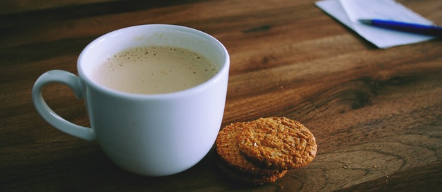 a cup of coffee accompanied by 2 cookies